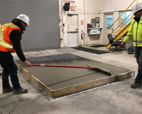 Dufferin Concrete employee demonstrating a Broom Finish on a sample concrete slab during the customer demo day