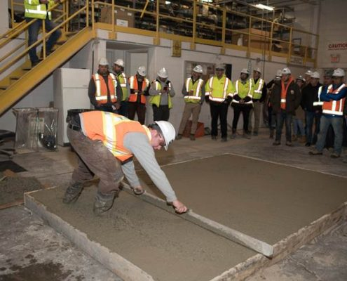 Duferin Concrete employee demonstrating how to Properly Place concrete on a sample concrete slab during demo day