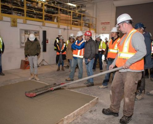 Dufferin Concrete employee demonstrating the use of a Roller Tamper (Jitterbug Roller) on a sample concrete slab